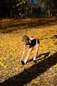 Jeune femme en bonne santé se réchauffant en étirant ses bras sur la route en plein air, séance de jogging dans le parc.