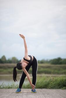 Une jeune femme en bonne santé se réchauffe à l'extérieur avant une séance d'entraînement au parc.