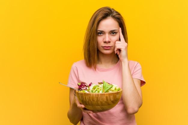 Jeune femme en bonne santé tenant une salade en pointant sa tempe avec le doigt, pensant, concentrée sur une tâche.