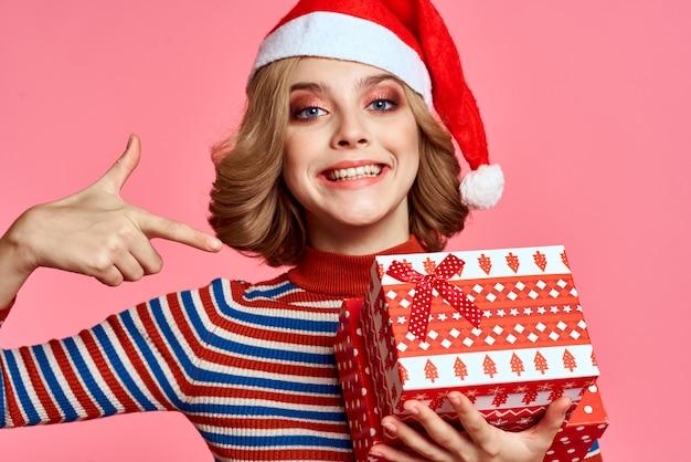 Jeune femme en bonnet de noel avec boîte-cadeau