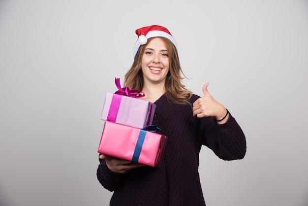 Jeune femme en bonnet de noel avec des coffrets cadeaux montrant un pouce vers le haut.