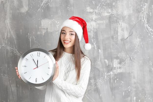 Jeune femme en bonnet de noel avec horloge sur fond grunge. notion de compte à rebours de noël