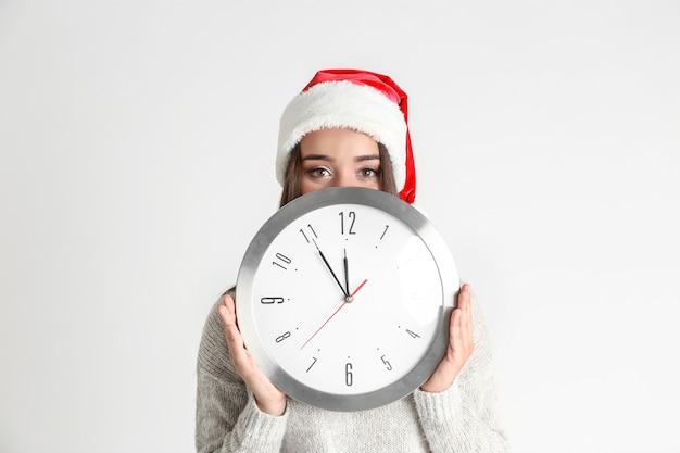 Jeune femme en bonnet de noel avec horloge. notion de compte à rebours de noël
