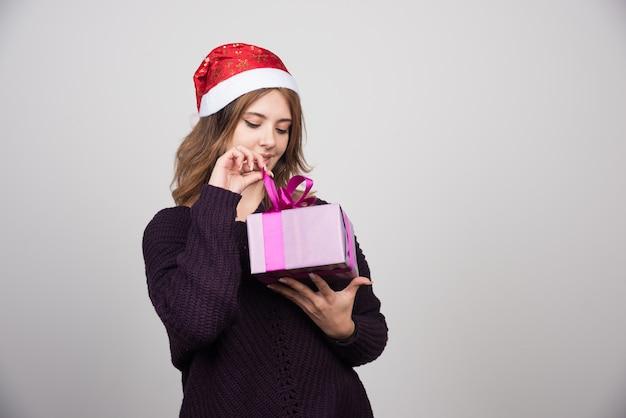 Jeune femme en bonnet de noel regardant une boîte-cadeau présente.