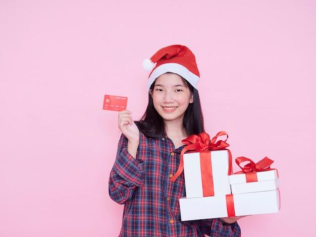 Jeune femme en bonnet de noel tenant la carte de crédit et les coffrets cadeaux sur le mur rose.