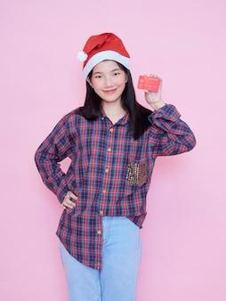 Jeune femme en bonnet de noel tenant une carte de crédit sur un mur rose.