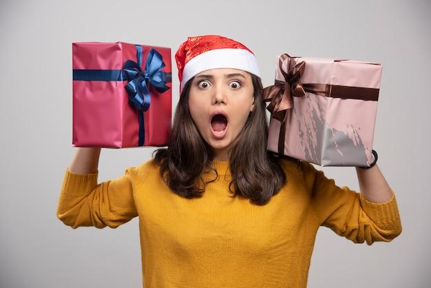 Jeune femme en bonnet de noel tenant dans les mains des coffrets cadeaux.
