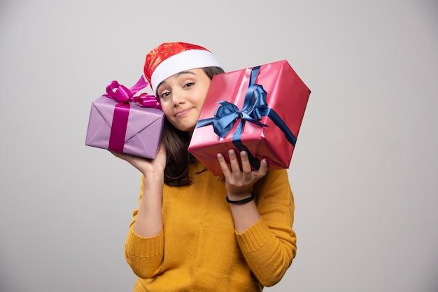Jeune femme en bonnet de noel transportant des cadeaux de noël.