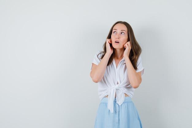 Jeune femme bouchant les oreilles avec les doigts en chemisier, jupe et à la curiosité