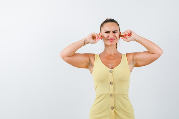 Jeune femme bouchant les oreilles avec les doigts en robe jaune et à la vue ennuyée, de face.