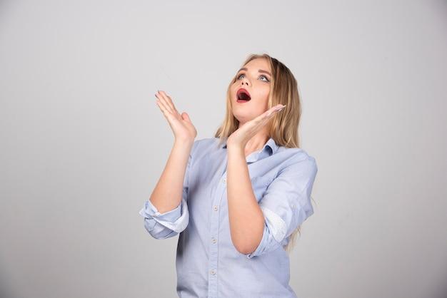 Jeune femme avec la bouche largement ouverte tenant les mains levées et levant les yeux.