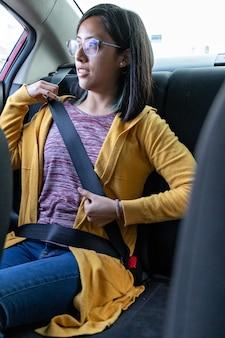 Une jeune femme bouclant sa ceinture de sécurité sur le siège arrière d'une voiture