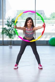 Jeune femme avec la boucle de hula dans la salle de gym dans le concept de santé