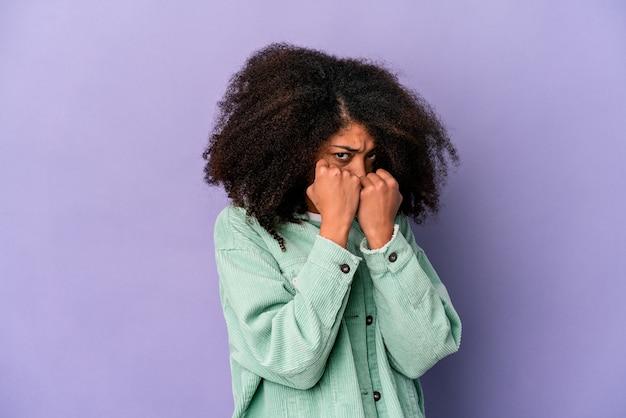 Jeune femme bouclée afro-américaine isolée sur fond violet jetant un coup de poing, la colère, les combats en raison d'une dispute, la boxe.