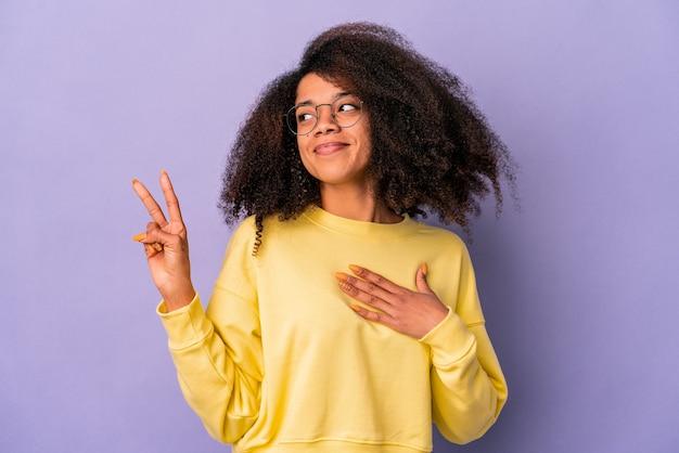 Jeune femme bouclée afro-américaine isolée sur le mur violet en prêtant serment, mettant la main sur la poitrine.