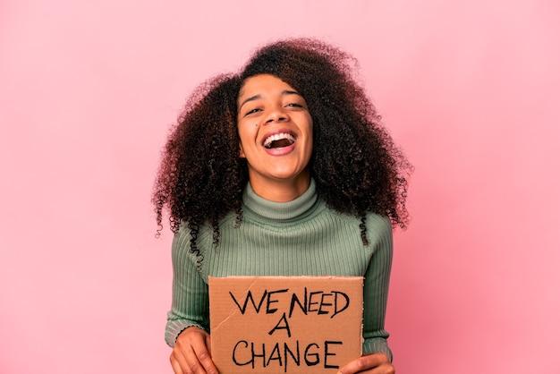 Jeune femme bouclée afro-américaine tenant un nous avons besoin d'une bannière de changement