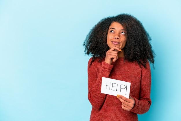 Jeune femme bouclée afro-américaine tenant une pancarte d'aide