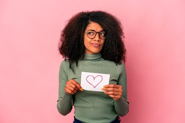 Jeune femme bouclée afro-américaine tenant un symbole du cœur sur une pancarte confuse, se sent douteuse et incertaine.