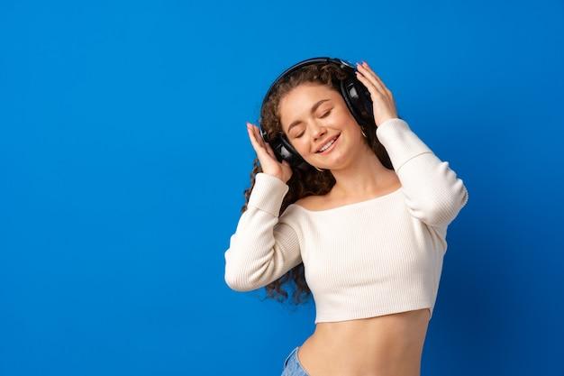 Jeune Femme Bouclée Attirante écoutant La Musique Avec Des écouteurs Sur Le Fond Bleu Photo Premium