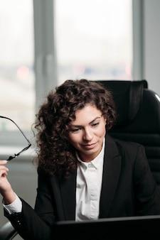 Jeune femme bouclée au bureau en vêtements d'affaires