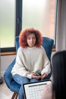 Jeune femme bouclée parlant à son psychothérapeute