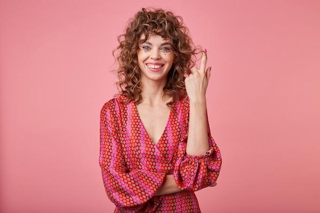 Jeune femme bouclée se dresse, souriant et tordant les cheveux sur le doigt, vêtue d'une robe rayée romantique