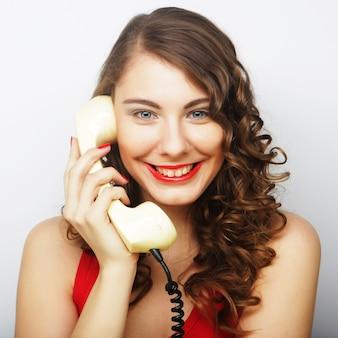 Jeune femme bouclée avec téléphone vintage.