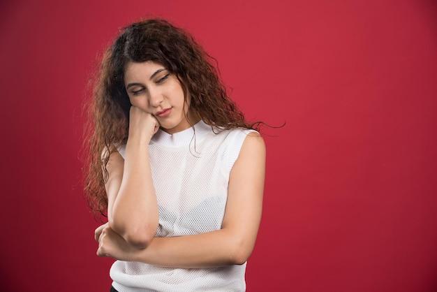 Jeune femme bouclée touchant doucement son visage avec la main levée sur le rouge.