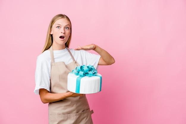 Jeune femme de boulanger russe tenant un délicieux gâteau choqué et étonné tenant un espace de copie entre les mains