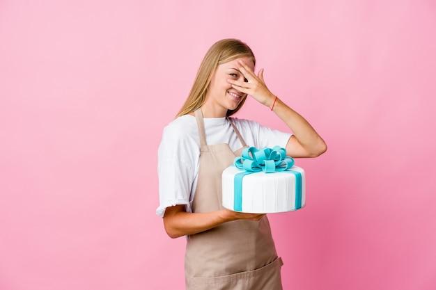 Jeune femme de boulanger russe tenant un délicieux gâteau clignote entre les doigts, gêné couvrant le visage.