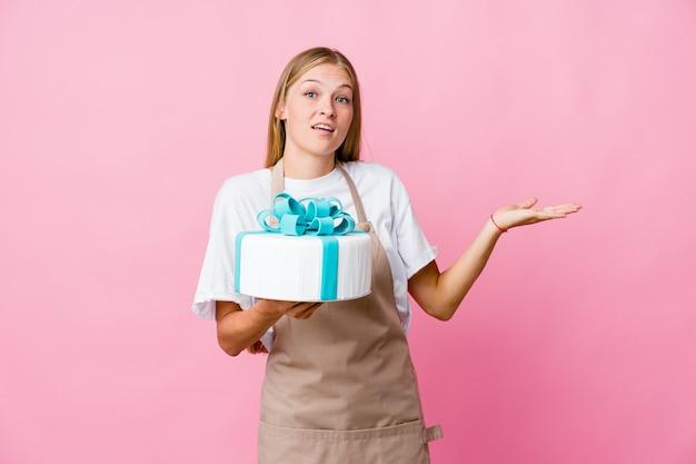 Jeune femme de boulanger russe tenant un délicieux gâteau doutant et haussant les épaules en geste de questionnement