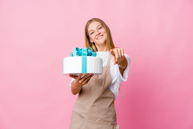 Jeune femme boulangère russe tenant un délicieux gâteau sourires joyeux pointant vers l'avant.