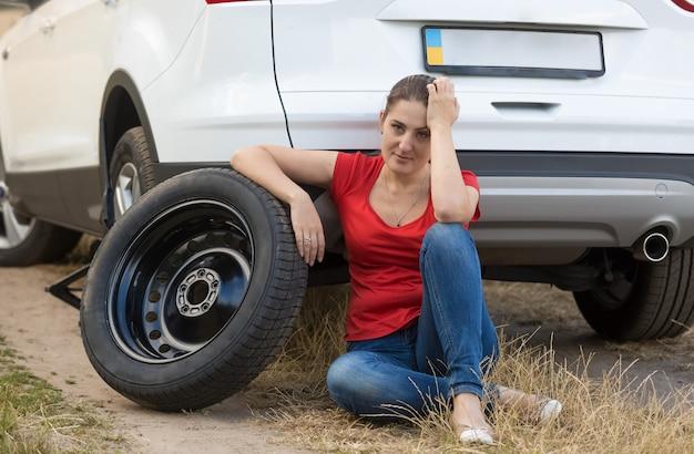 Jeune femme bouleversée assise sur le sol à côté de la roue de secours