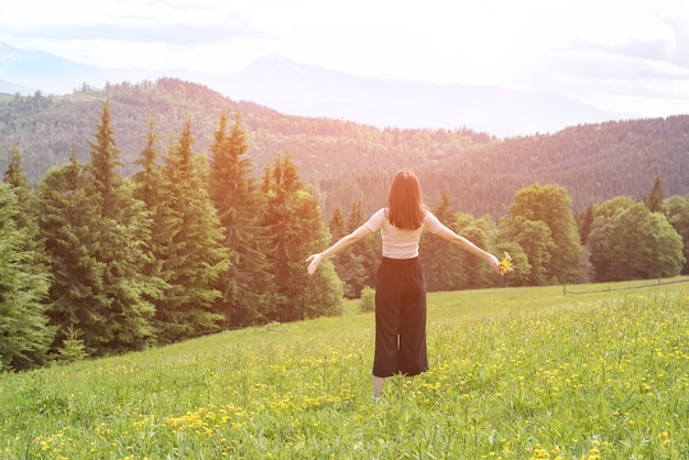 Jeune femme avec un bouquet de fleurs et les bras grands ouverts debout dans la prairie. forêt et montagnes en arrière-plan. vue arrière