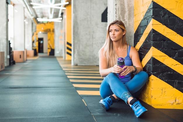 Jeune femme avec une bouteille d'eau assis dans une salle de sport