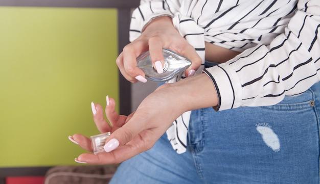 Jeune femme avec une bouteille de parfum à la maison.