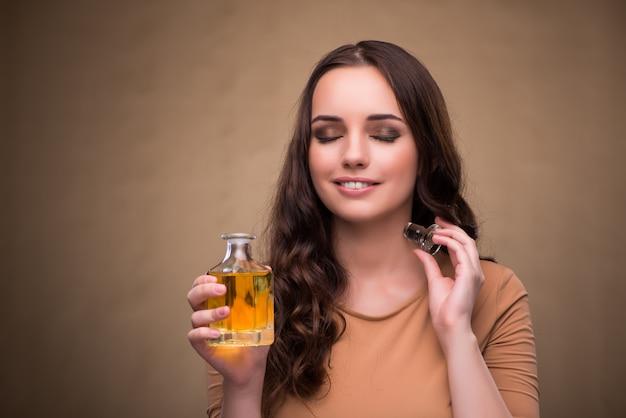 Jeune femme avec une bouteille de parfum