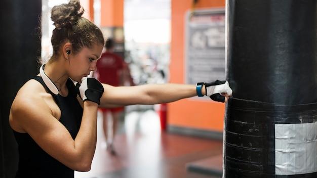Jeune femme boxe dans la salle de gym