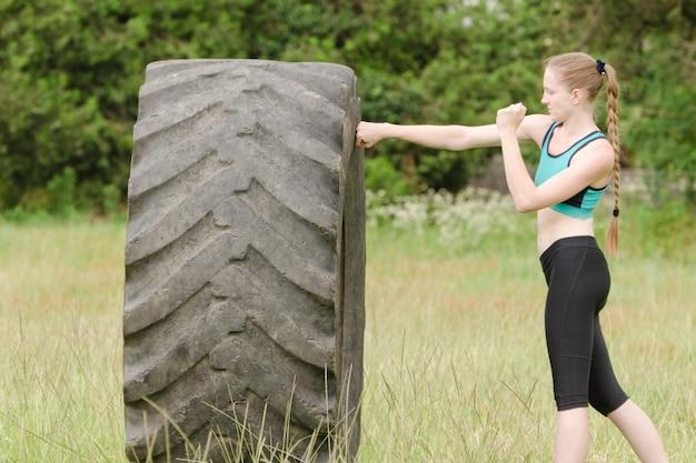 Jeune femme boxe avec le pneu.