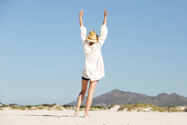 Jeune femme avec les bras levés marchant sur la plage