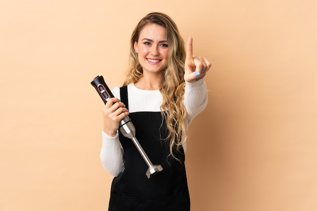 Jeune femme brésilienne à l'aide d'un mélangeur à main isolé sur beige montrant et en soulevant un doigt