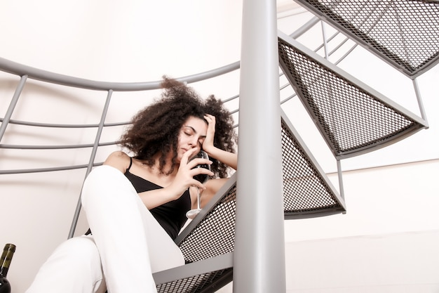 Une jeune femme brésilienne assise sur les escaliers avec un verre de vin rouge.