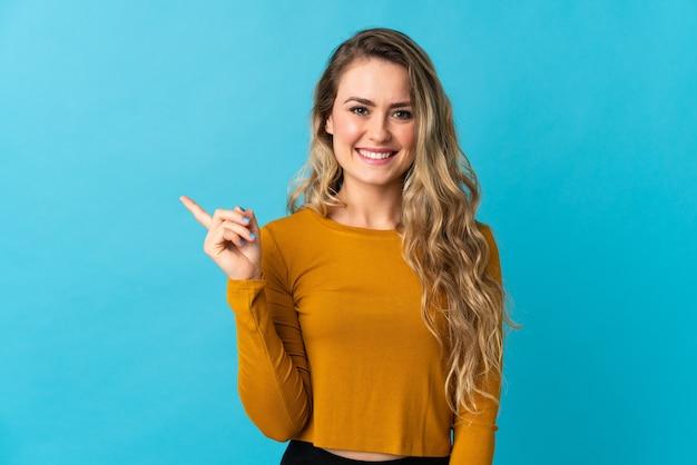 Jeune femme brésilienne isolée sur bleu pointant vers le côté pour présenter un produit