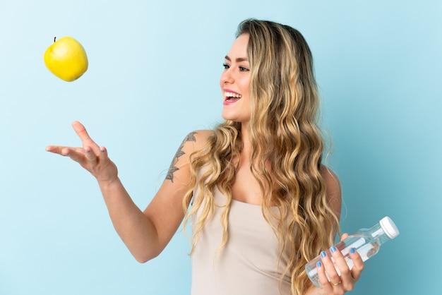 Jeune femme brésilienne isolée sur bleu avec une pomme et avec une bouteille d'eau