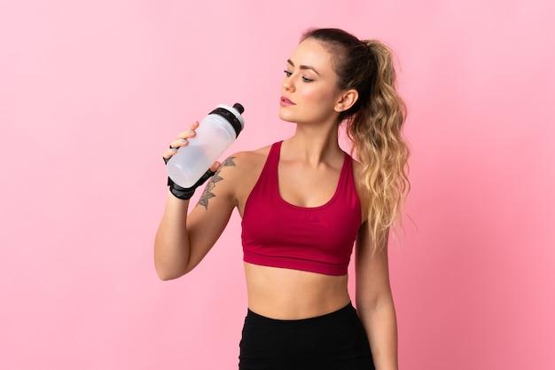 Jeune femme brésilienne isolée avec bouteille d'eau de sport