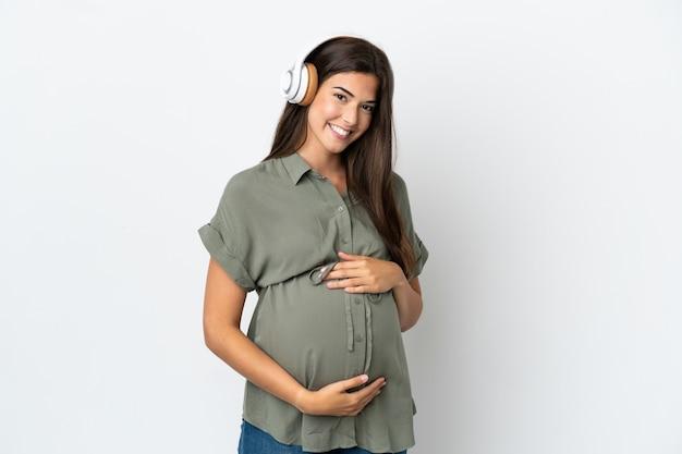 Jeune femme brésilienne isolée sur fond blanc enceinte et écoute de la musique