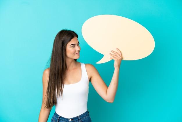 Jeune femme brésilienne isolée sur fond bleu tenant une bulle de dialogue vide