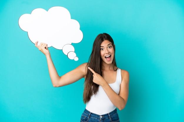 Jeune femme brésilienne isolée sur fond bleu tenant une bulle de pensée avec une expression surprise
