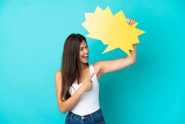 Jeune femme brésilienne isolée sur fond bleu tenant une bulle vide et la pointant