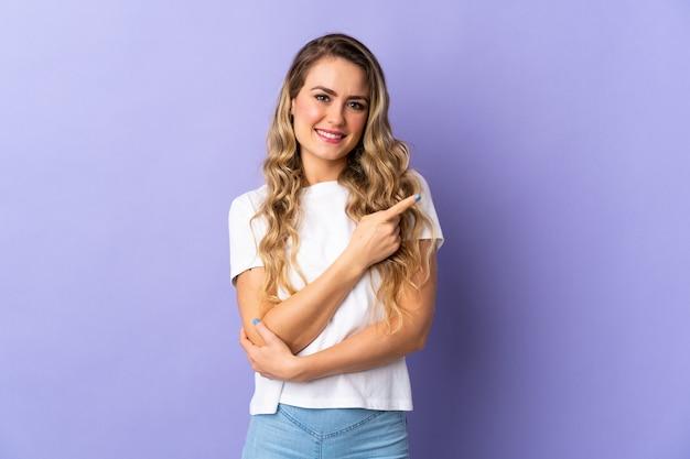 Jeune femme brésilienne isolée sur fond violet pointant vers le côté pour présenter un produit